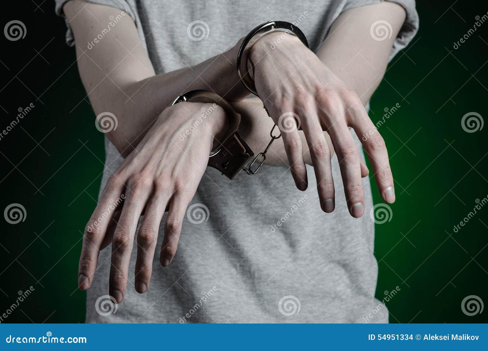 Więźniarski i skazujący temat: mężczyzna z kajdankami na jego rękach w szarej koszulce i niebieskich dżinsach na ciemnozielonym t