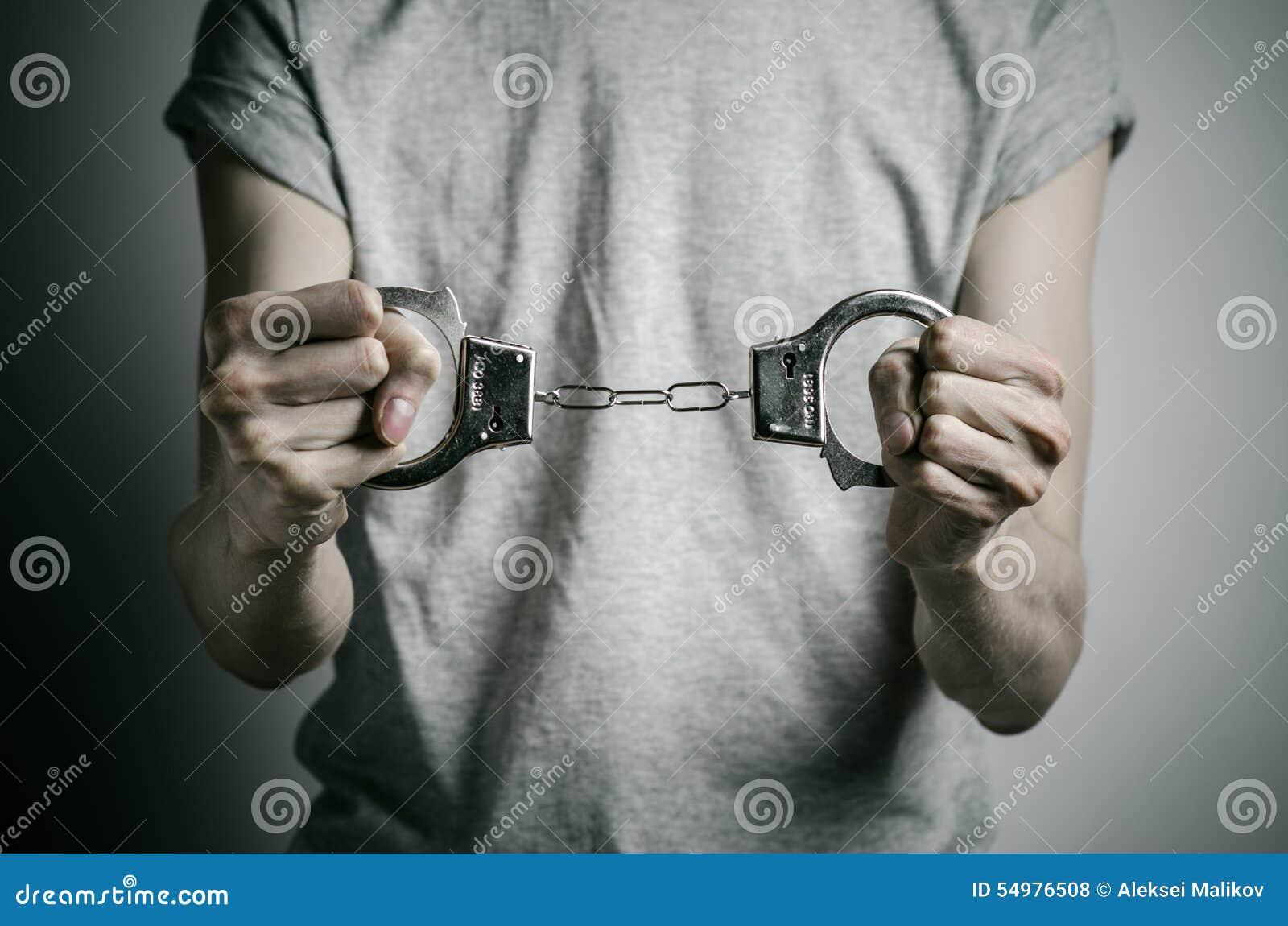 Więźniarski i skazujący temat: mężczyzna z kajdankami na jego rękach w szarej koszulce na szarym tle w studiu, stawia kajdanki da