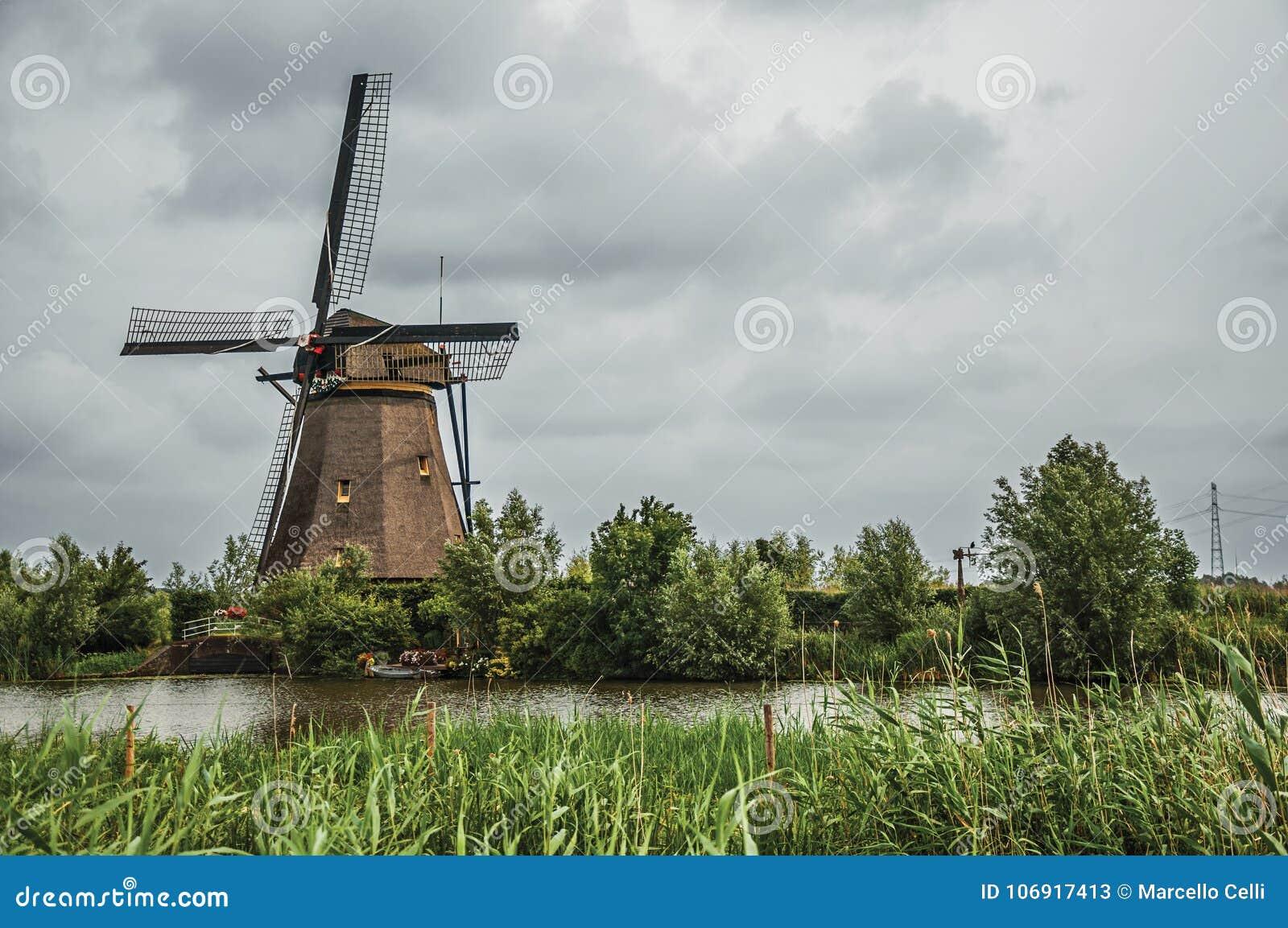 Wiatraczek i wysocy krzaki na banku wielki kanał w chmurnym dniu przy Kinderdijk