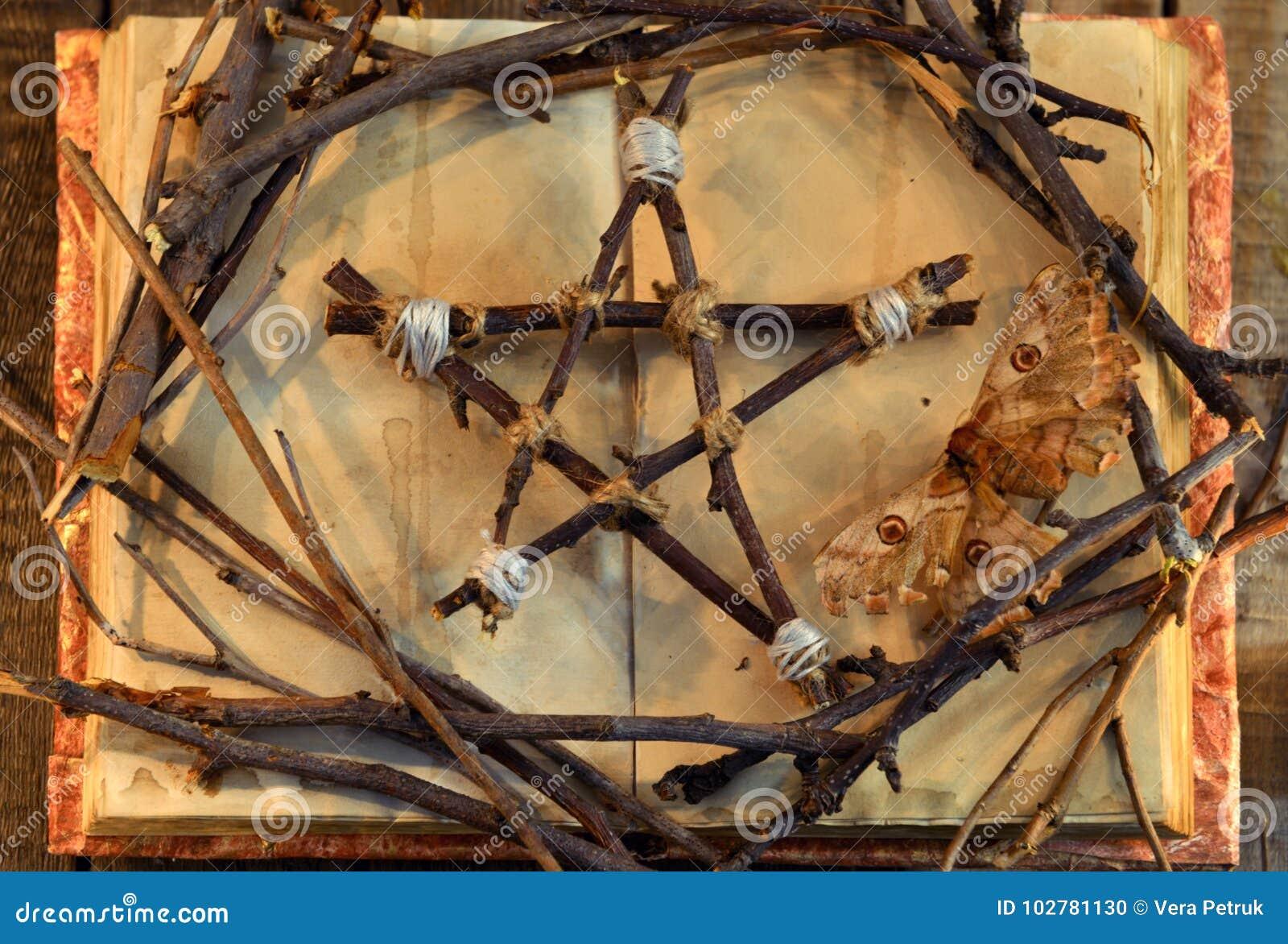 Wicca pentagram, mot - doodssymbool, en boomtakken op open boek met sjofele pagina s in kaars lichte, hoogste mening