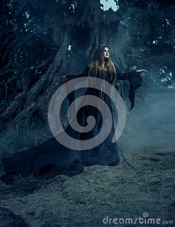 Wicked witch in a long vintage dress, wandering through foggy forest