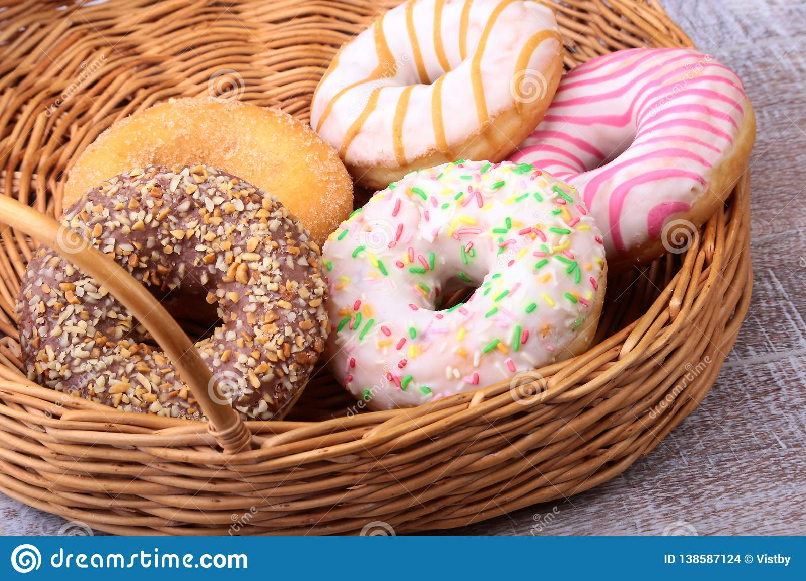 Wicker basket with assorted delicious homemade doughnuts in the glaze, colorful sprinkles and nuts .