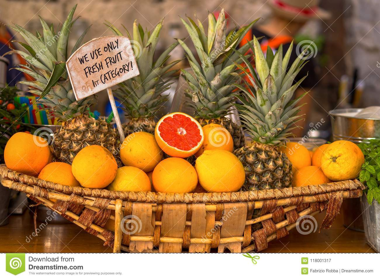 Wicker basket with oranges and pineapples.
