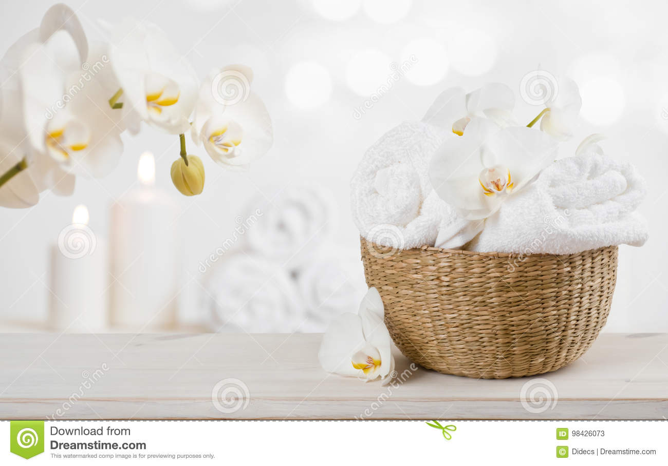 Wicker basket with spa towels on table over abstract background