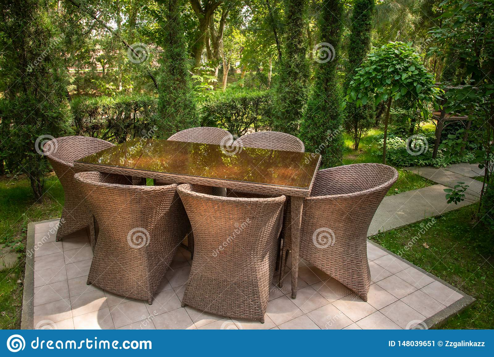 Wicker chairs and table are in the garden near trees