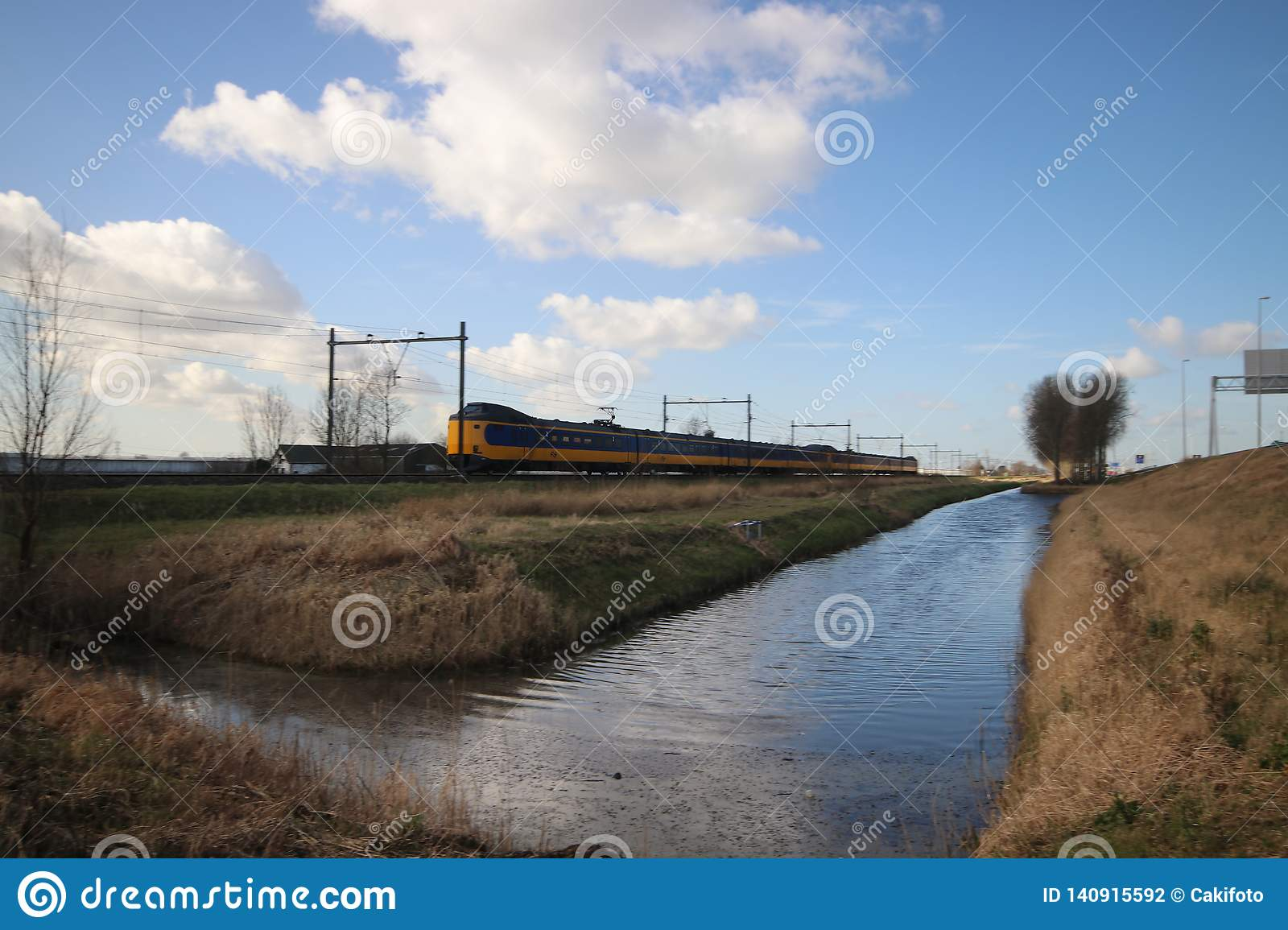 Wide angle overview of a koploper ICM intercity train on the track fron the hague heading to Gouda.