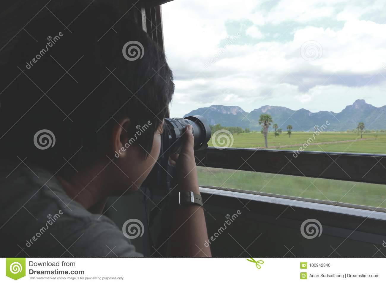 Wide angle shot of young Asian tourist taking a photo of scenic nature mountain with professional camera in the train