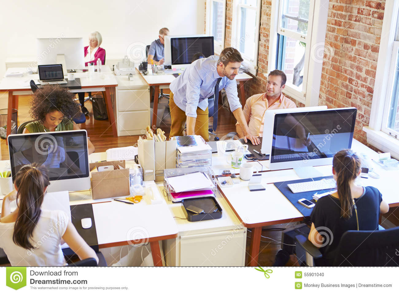 wide angle view of busy design office with workers at