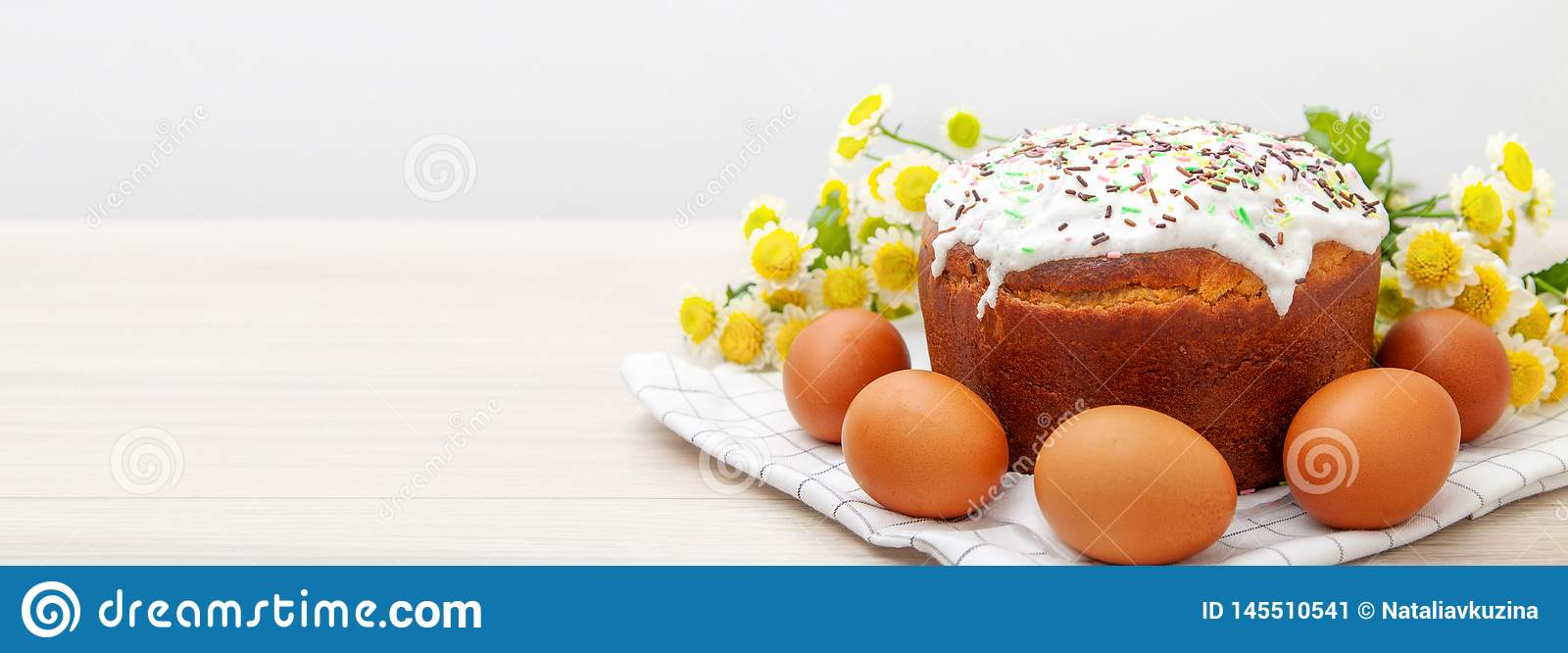Wide banner with Easter cake and colored eggs yellow flower blossoms on background. Holiday food and easter concept. Copyspase for