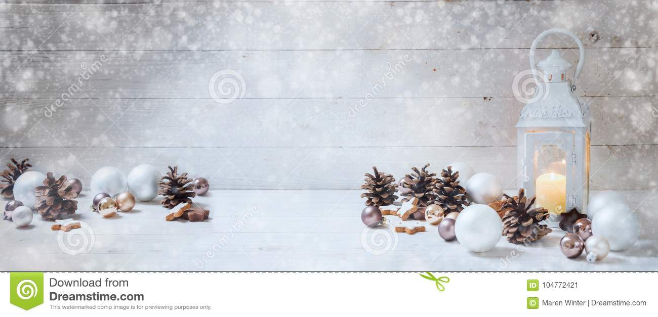 Wide christmas background with a candle light lantern, baubles,