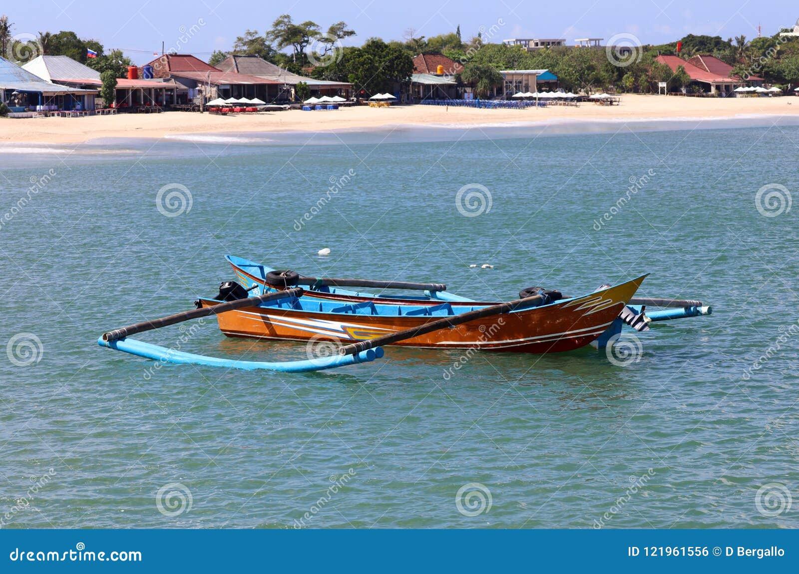 Beautiful picture of fishing boats at Jimbaran Bay at Bali Indonesia, beach, ocean, fishing boats and airport in photo.
