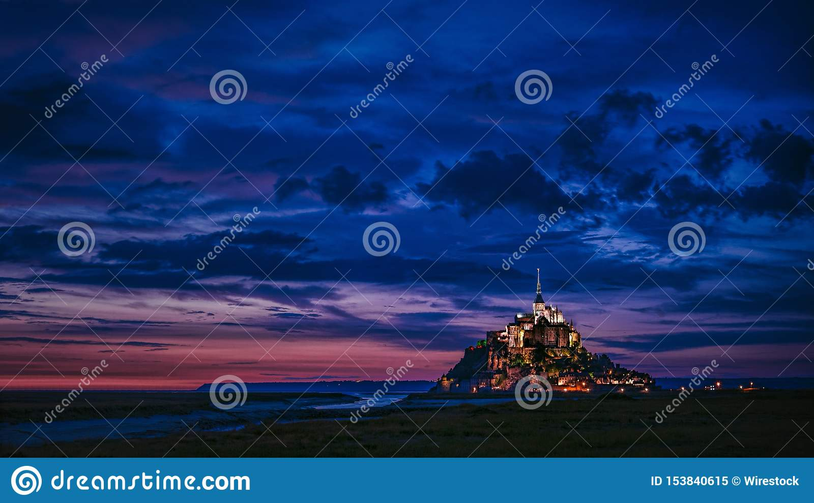 Wide shot of an illuminated castle in the distance with amazing blue clouds in the sky