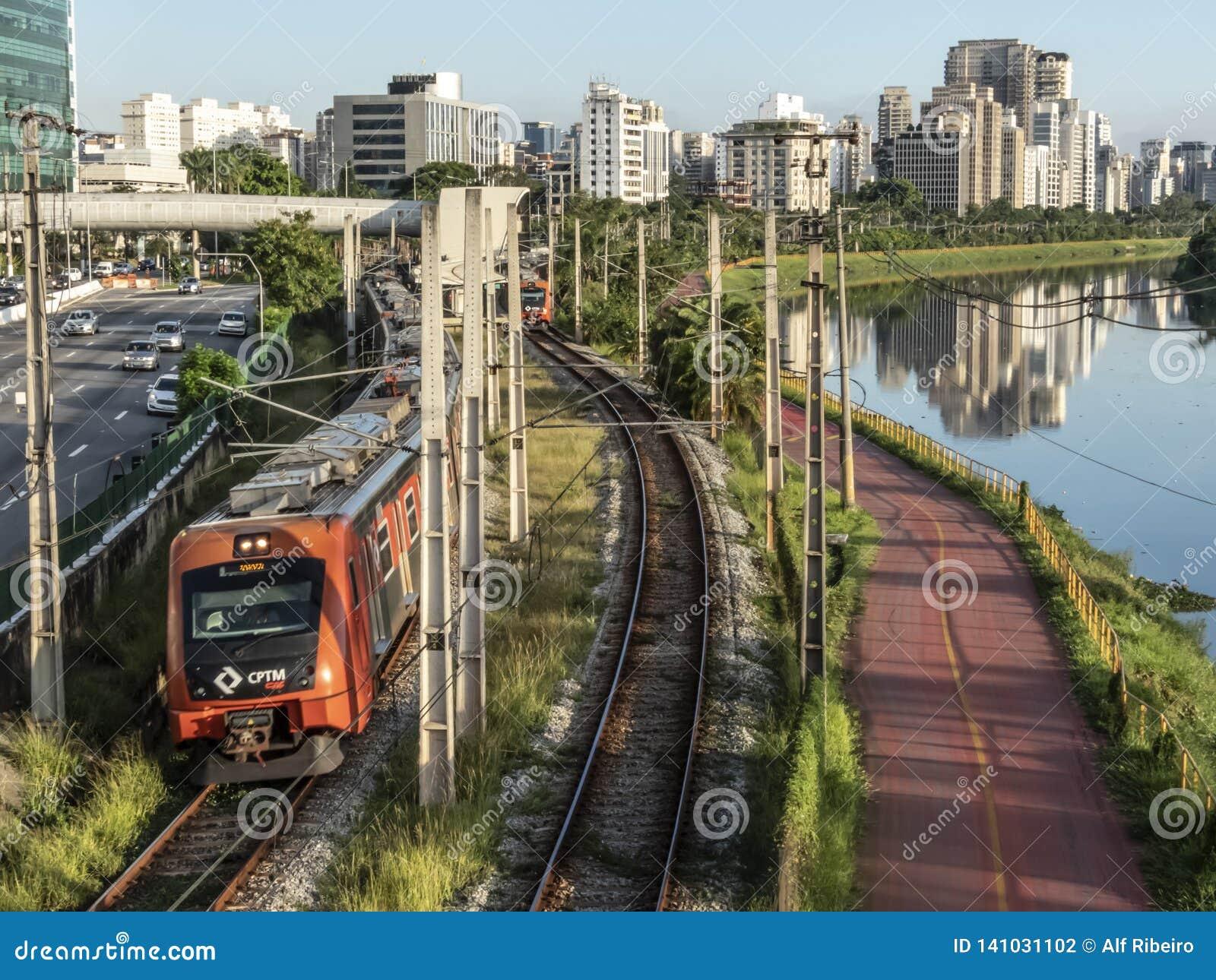 Widok budynki, CPTM pociąg, ruch drogowy pojazdy i rzeka w Brzeżnej Pinheiros rzeki alei,