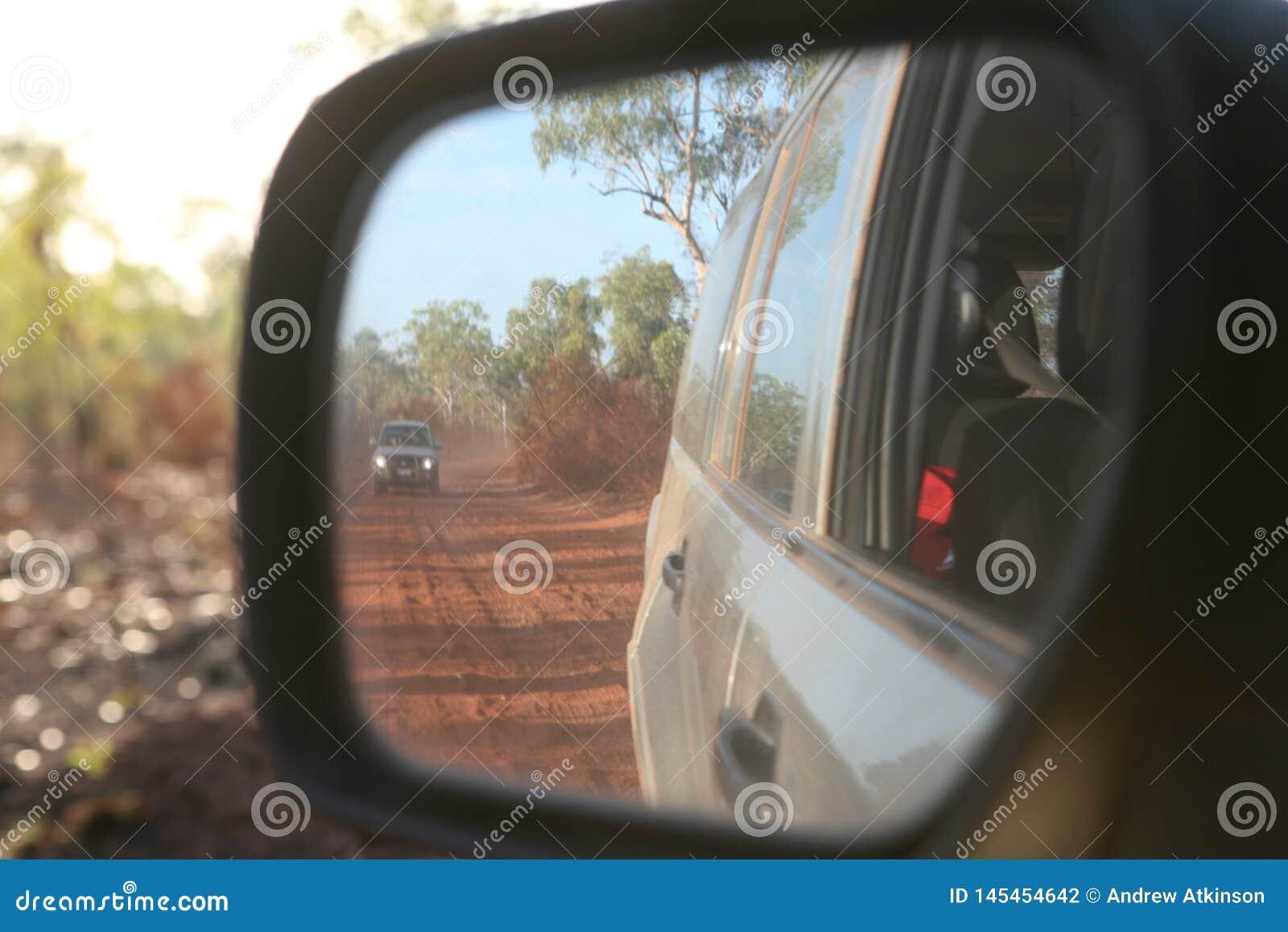 Widok cztery kół przejażdżki pojazd w za tylni lustrem wzdłuż czerwonej, panwiowej, zakurzonej drogi w Australia,
