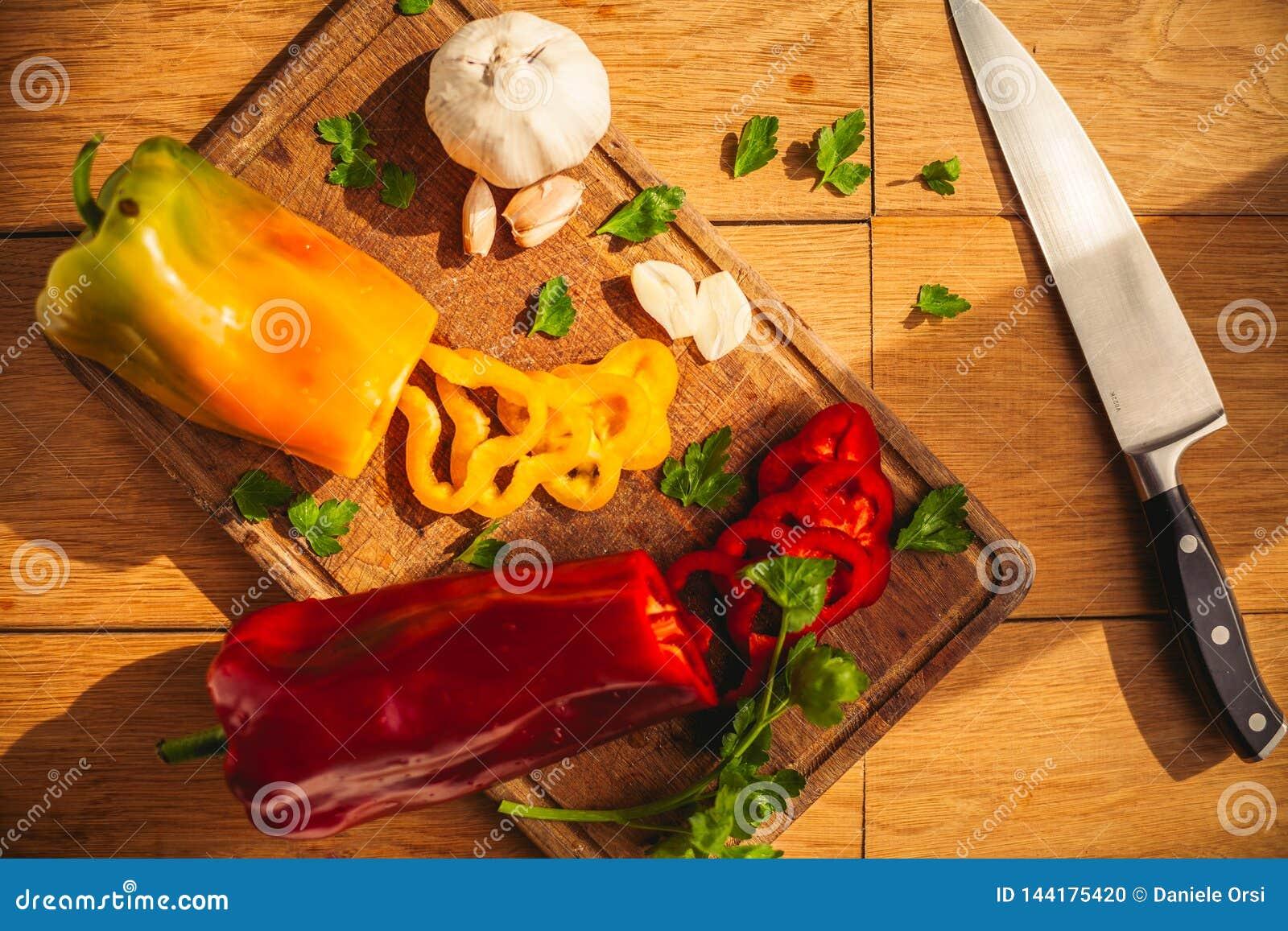 Widok dwa pieprzu na ciapanie desce z niektóre składnikami wokoło one: czosnek, pietruszka, olej