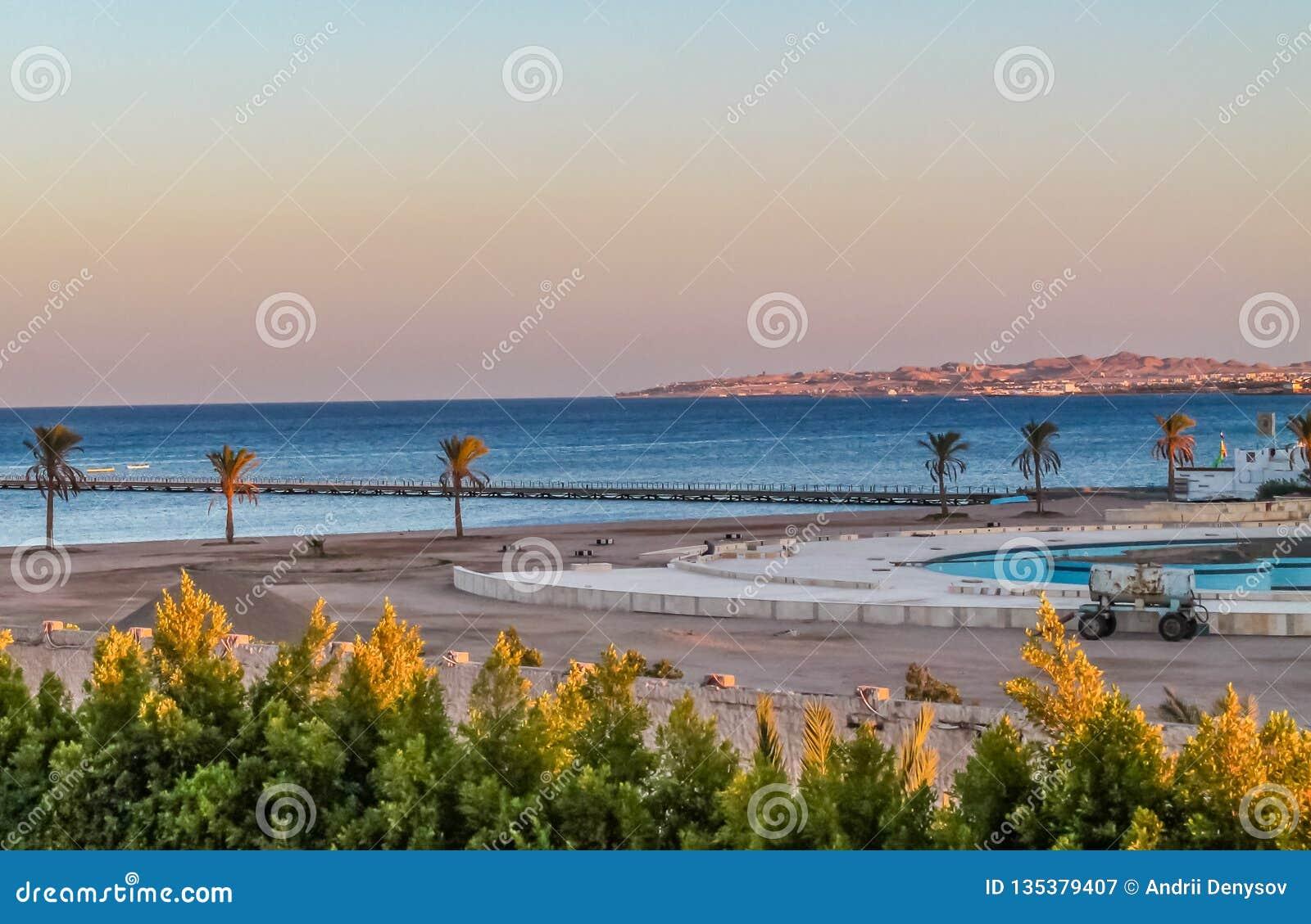 Widok hotel's rekreacyjny teren na plażowym i dennym brzeg, drzewka palmowe pod niebieskim niebem słoneczny dzień