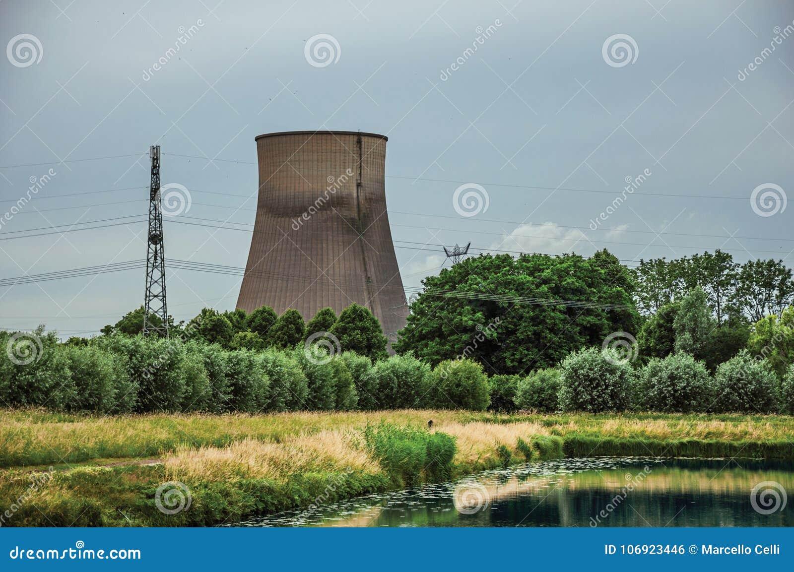 Widok kanał i ogródy z elektrownią jądrową w tle na chmurnym dniu blisko wioski Geertruidenberg,