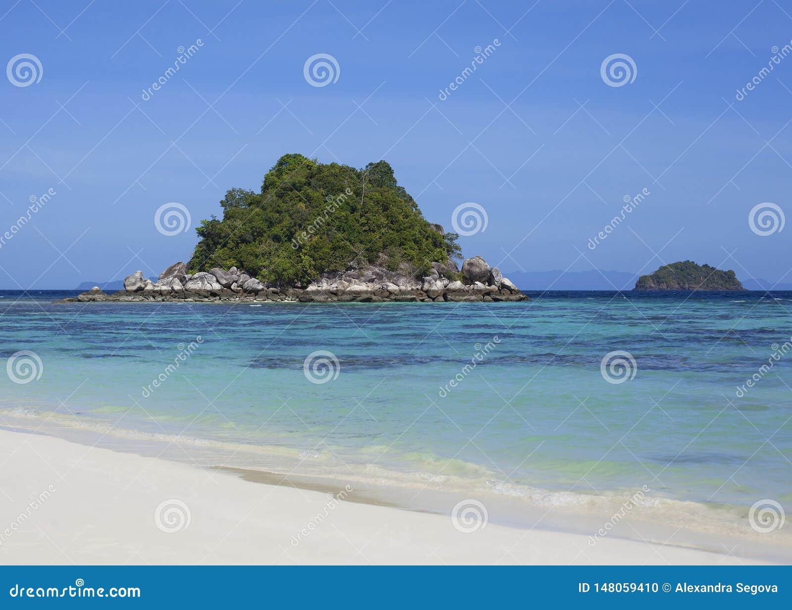 Widok na bezludnej wyspie w błękitnej lagunie od białej piasek plaży