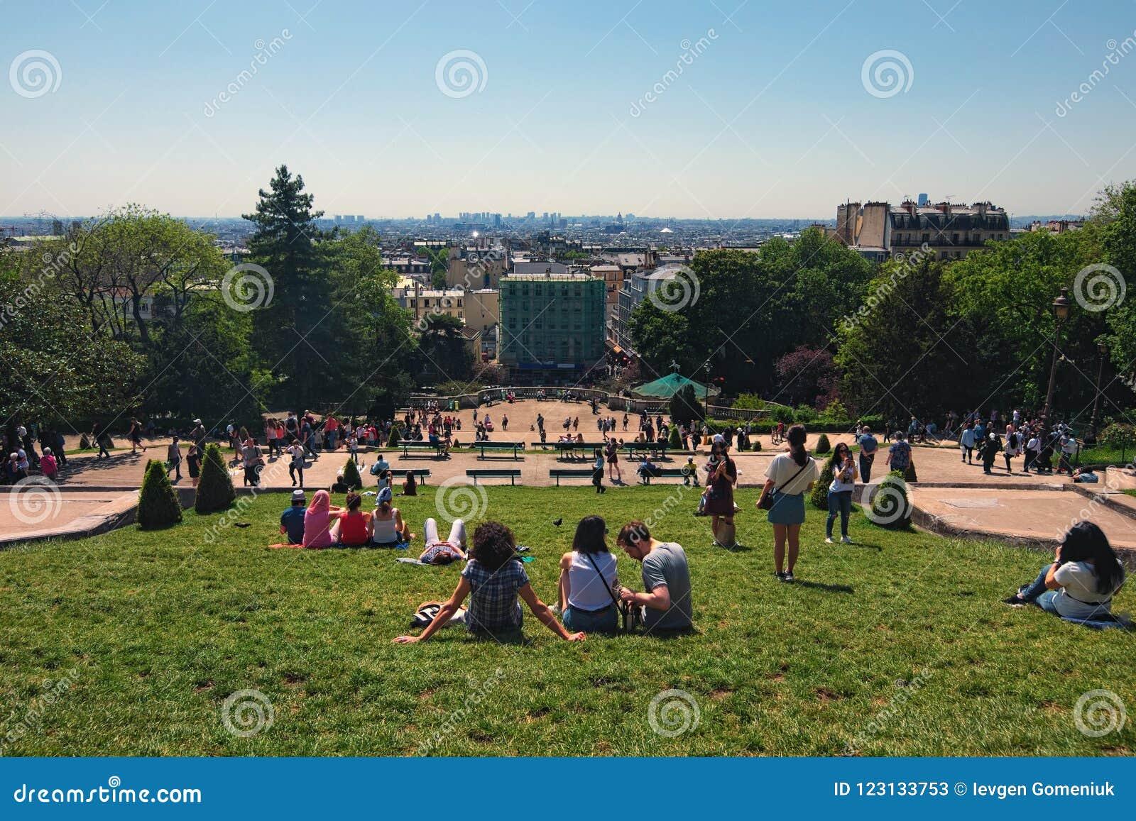 Widok od Montmartre wzgórza zielony gazon przed Sacre Coeur kościół z turystami relaksuje i cieszy się