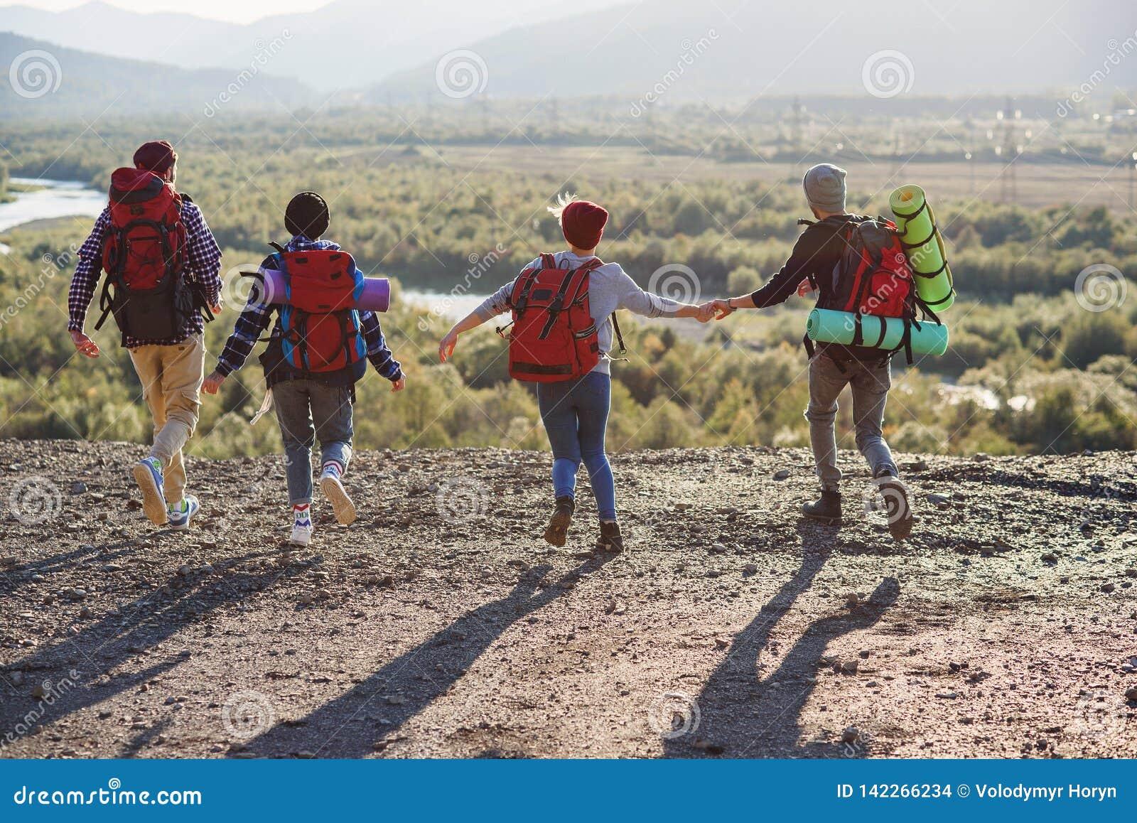 Widok od plecy cztery modnisia przyjaciela z podróż plecaka mienia rękami naprzód i bieg góra na zmierzchu