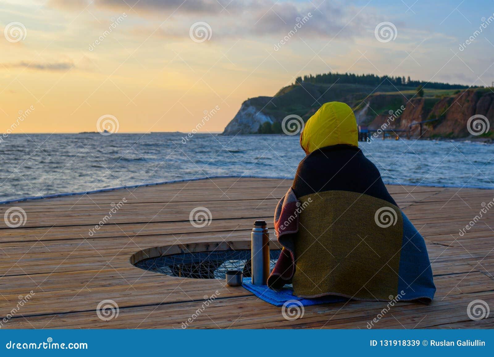 Widok od plecy, kobieta w powszechnym obsiadaniu na molu i pić od termosu, ogląda świt