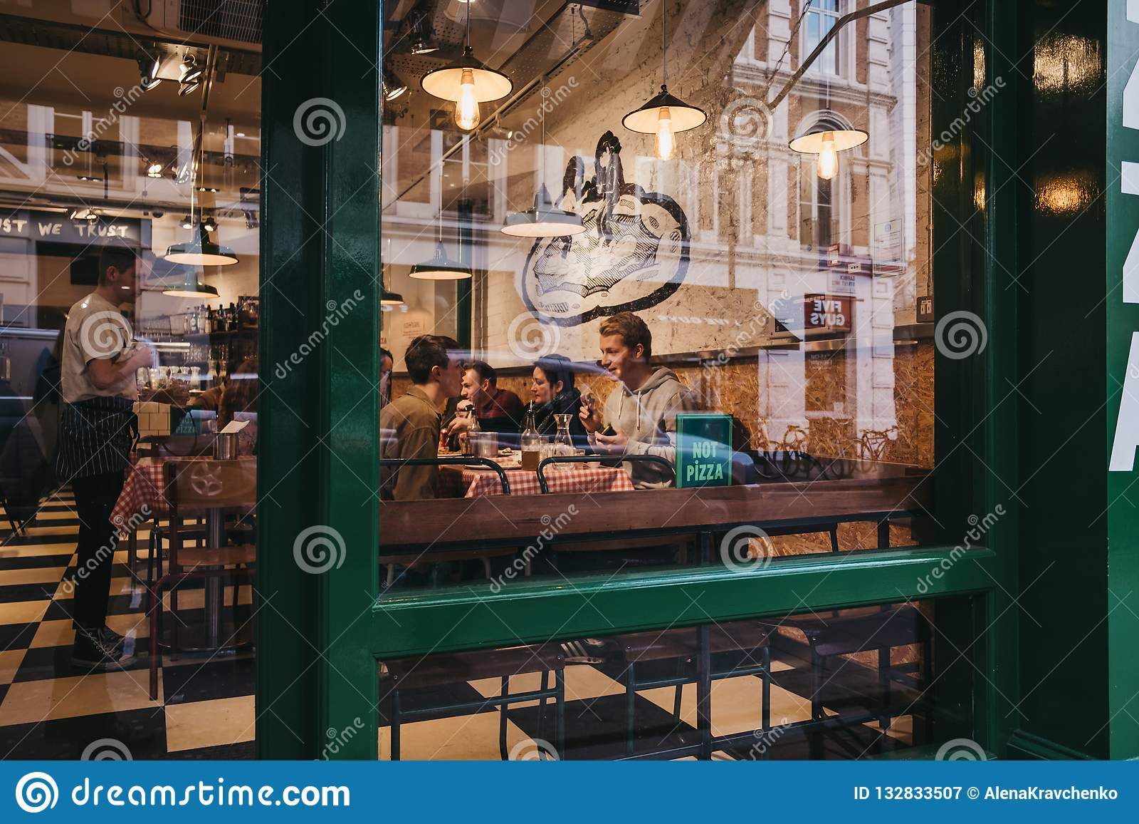 Widok przez okno ludzie wśrodku restauracji w Covent Garden, Londyn, UK