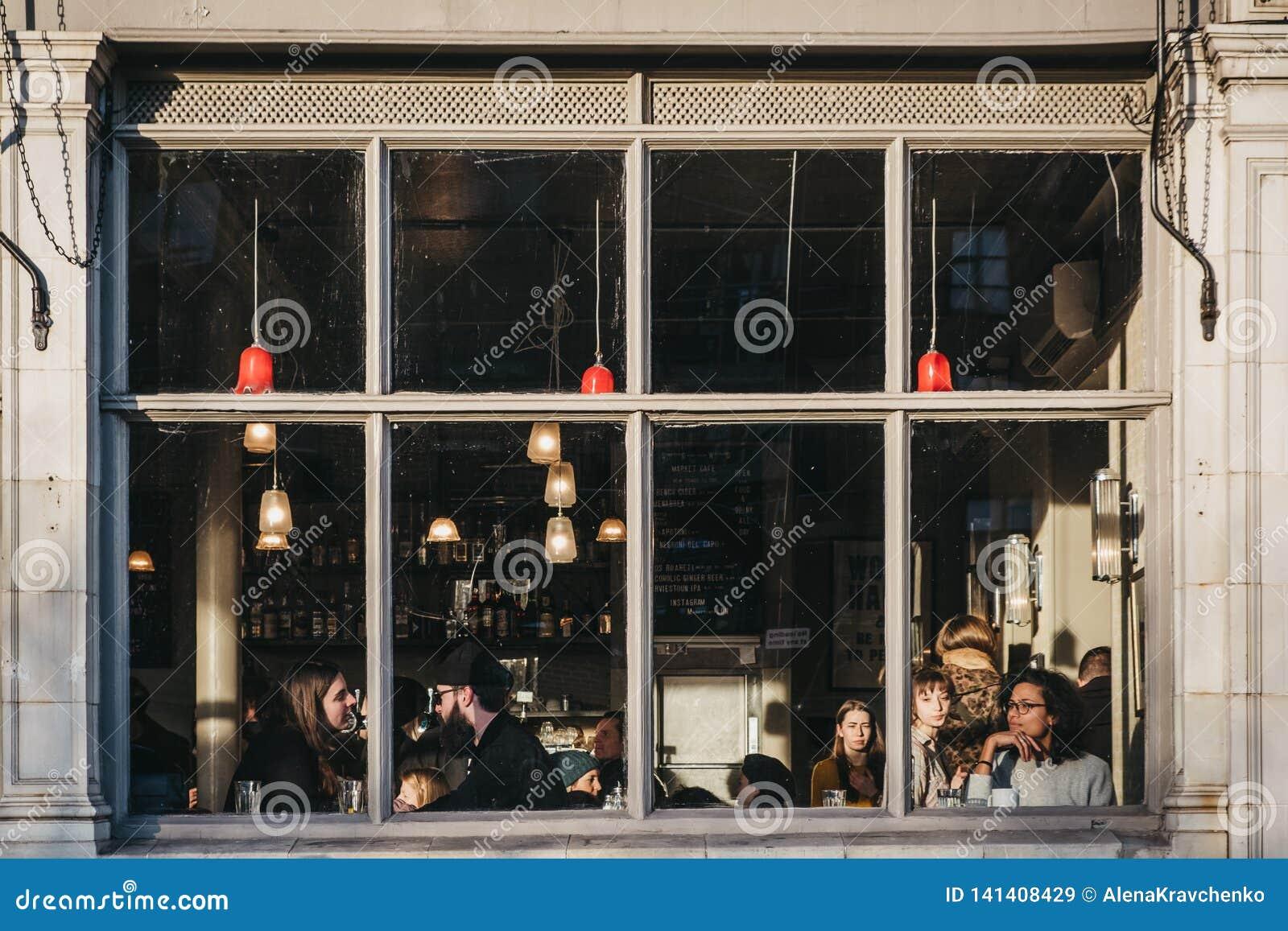 Widok przez okno ludzie wśrodku Targowego Cukiernianego pubu na Broadway rynku, Londyn, UK