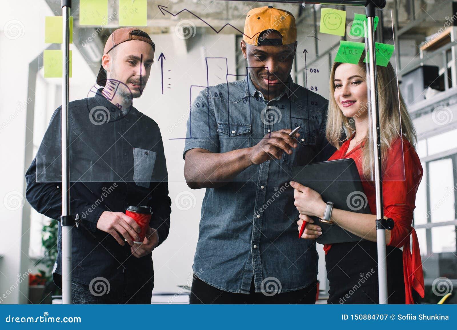 Widok przez szklanej ściany Kreatywnie Afrykański mężczyzna, Kaukaski mężczyzna i kobieta używamy pocztę ja zauważa dzielić pomys