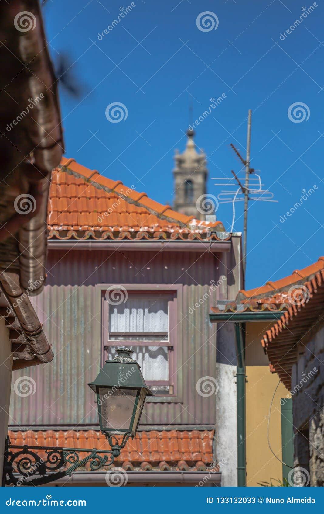 Widok przy tradycyjni miastowi budynki na Porto śródmieściu, zamazany Clerigos wierza na tle