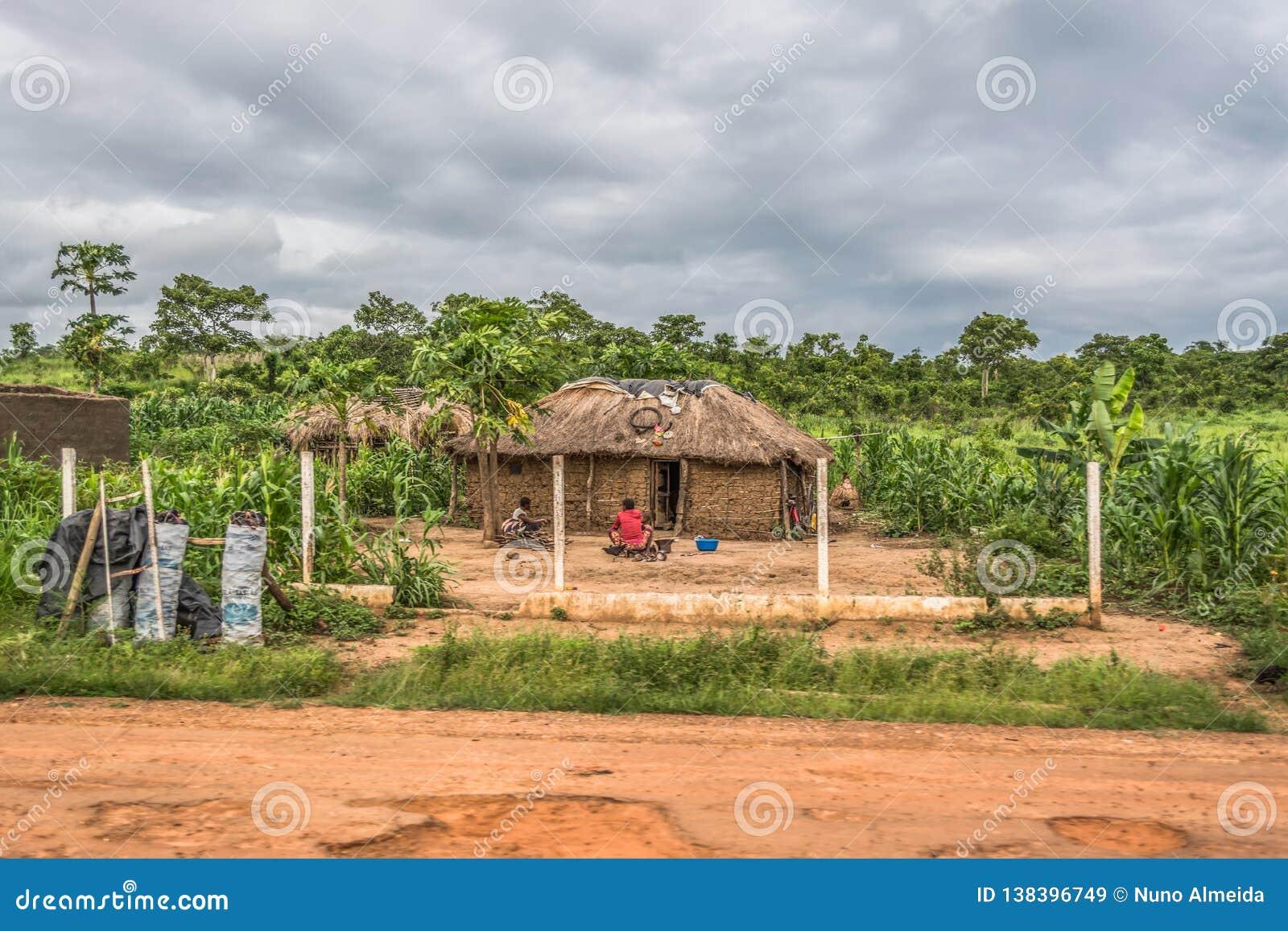 Widok tradycyjna wioska, dwa kobiety i dziecka obsiadanie przed pokrywającym strzechą domem z ścianami, dachu, terakoty i słomy