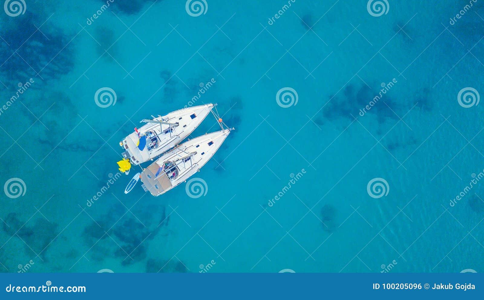 Widok z lotu ptaka dwa żeglowanie łodzi zakotwicza obok rafy
