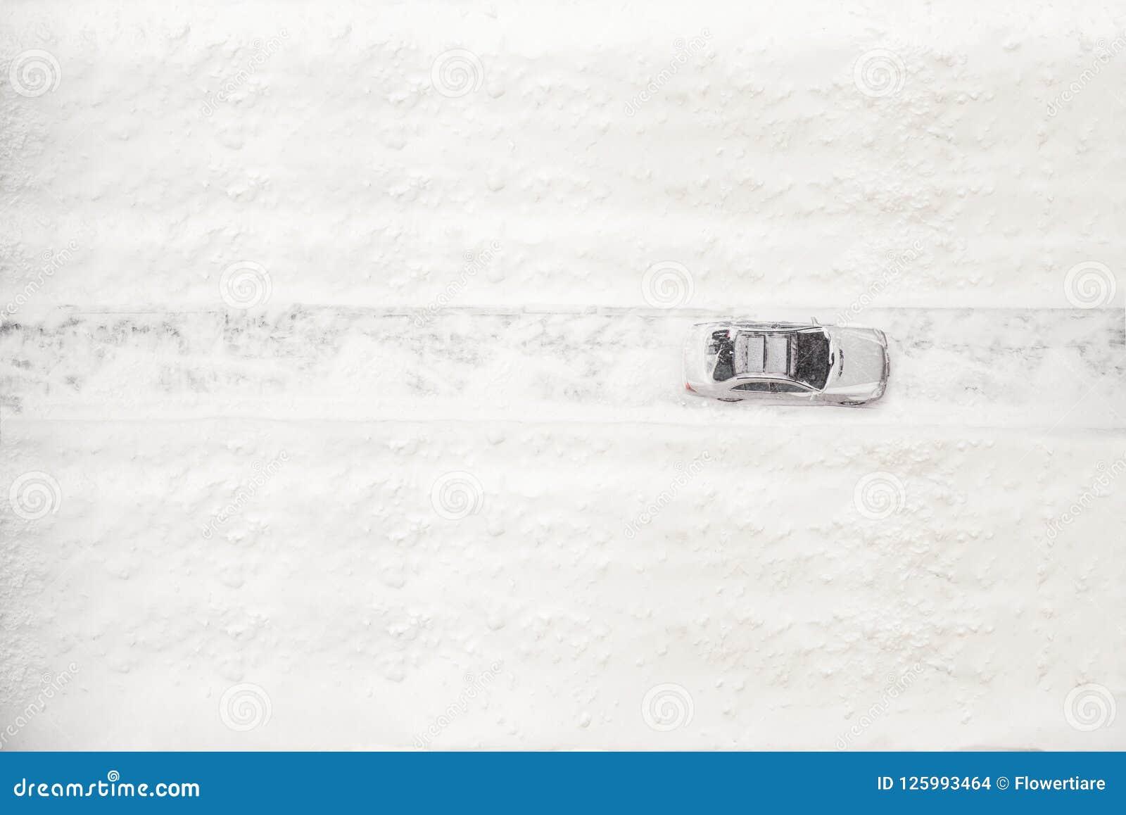 Widok z lotu ptaka na śnieżny samochodowy poruszającym na drodze przy zima czasem Sezonowy opad śniegu