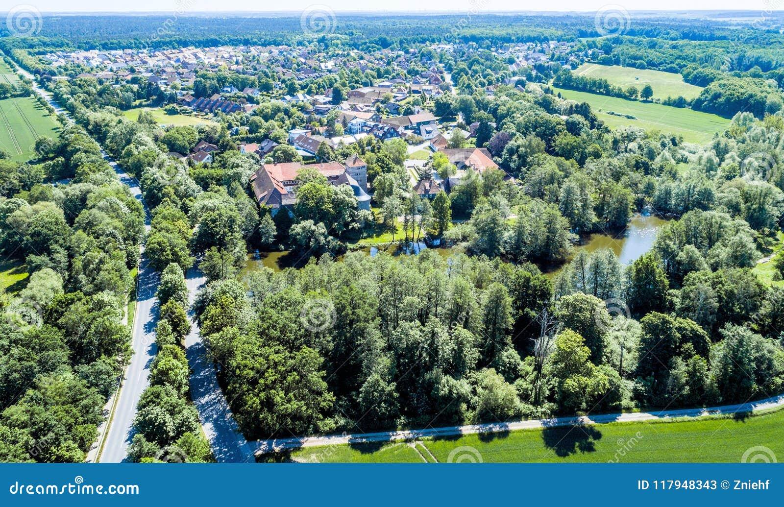 Widok z lotu ptaka Niemiecka wioska z małym lasem, kasztel w przedpolu, stawowy i moated