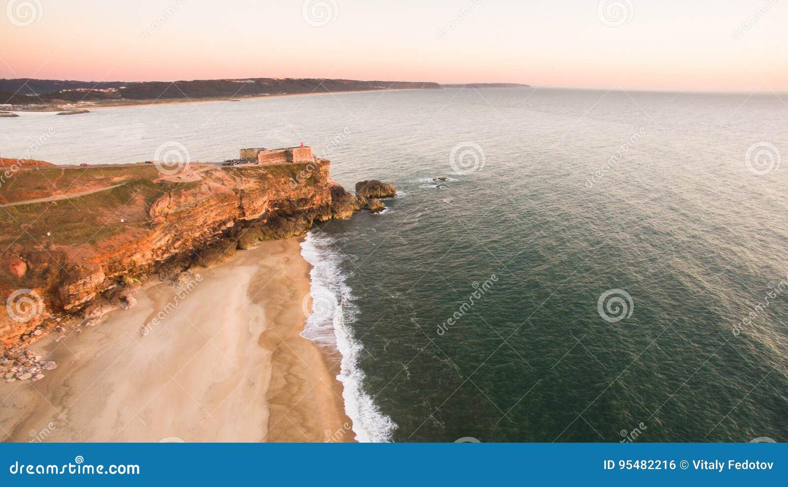 Widok z lotu ptaka ocean i Nazare latarnia morska przy zmierzchem, Portugalia