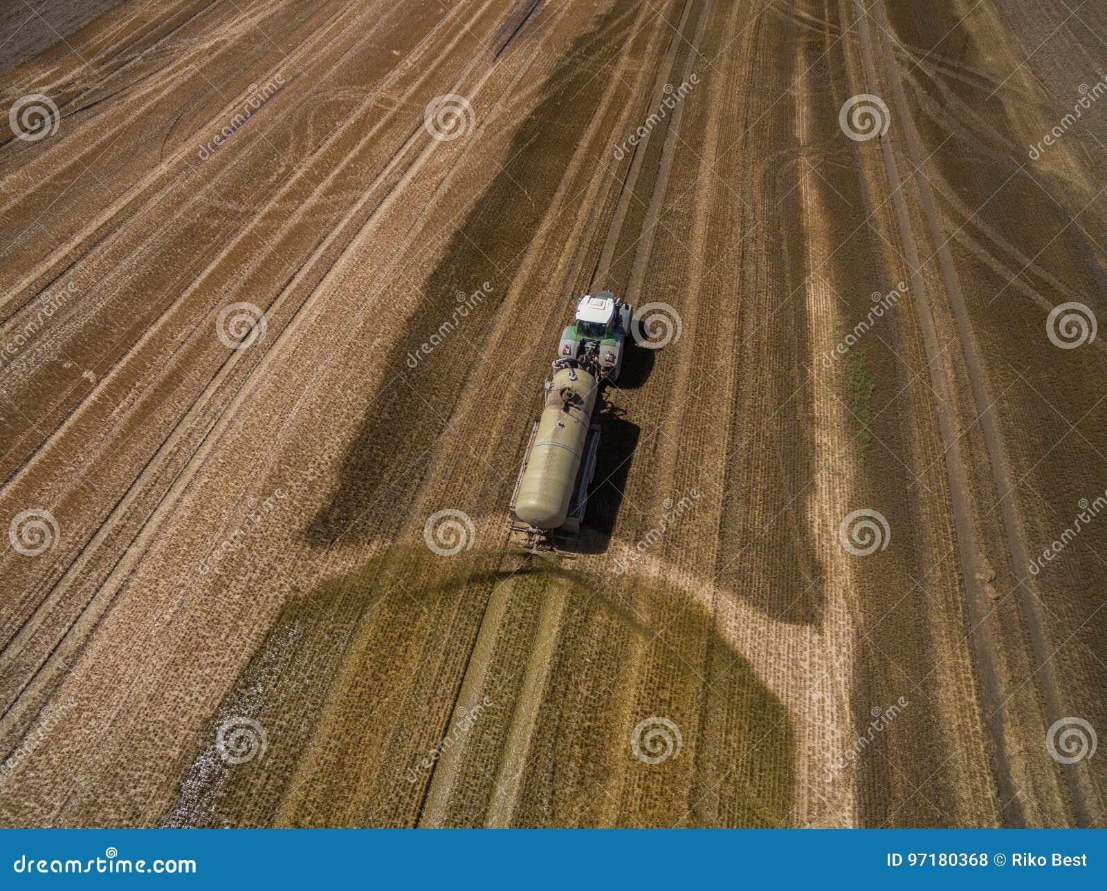 Widok z lotu ptaka uprawia ziemię ciągnik z przyczepą nawozi świeżo zaoranego agriculural pole z nawozem