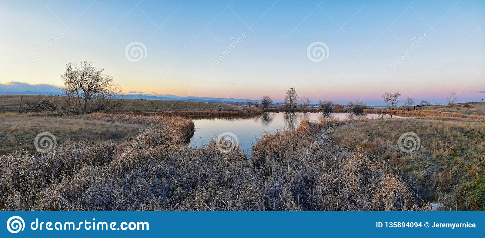 Widoki Josh's Stawowa chodząca ścieżka, Odbija zmierzch w Broomfield Kolorado otaczający ożypałkami, równiny i Skalistej góry l