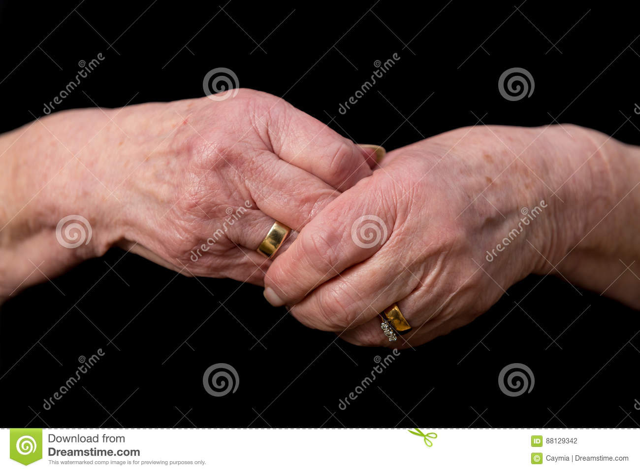Widows Hands Clasped In Grief On A Black Background. Stock Photo ...