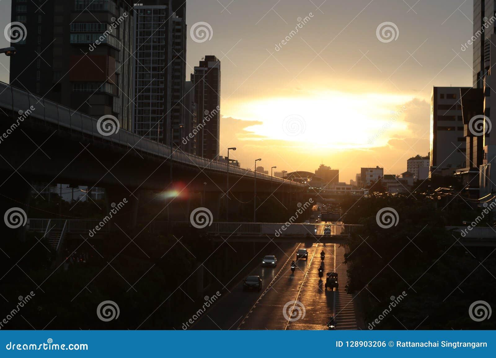 Wieczór wschód słońca koloru złocisty niebo, chmurny i ludzie iść do domu odgórny widok na niebo dworcu