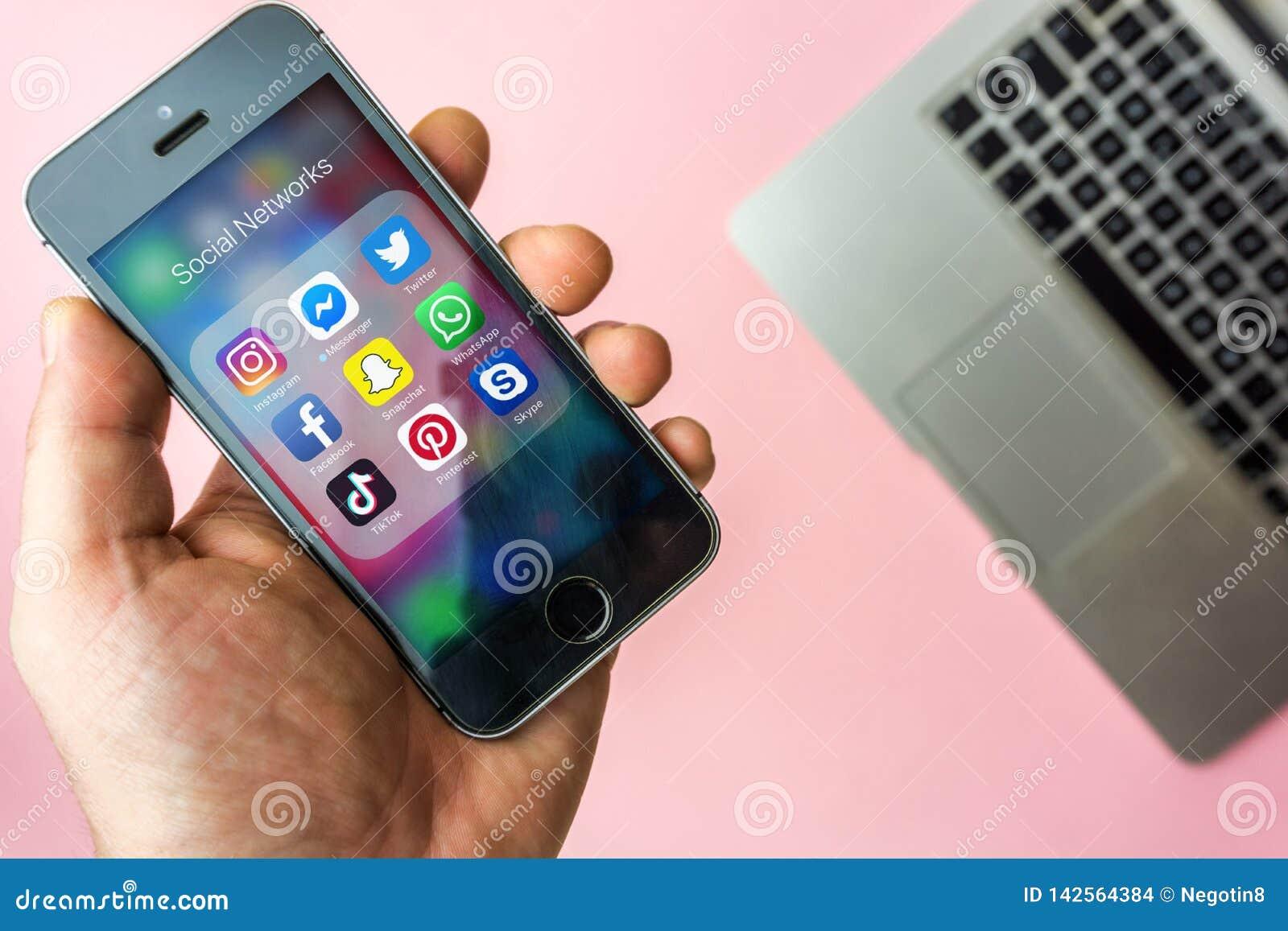 Wiedeń Austria, Marzec - 20 2019, kobieta trzyma Apple SE z ikonami ogólnospołeczni środki na ekranie Ogólnospołeczni środki są p