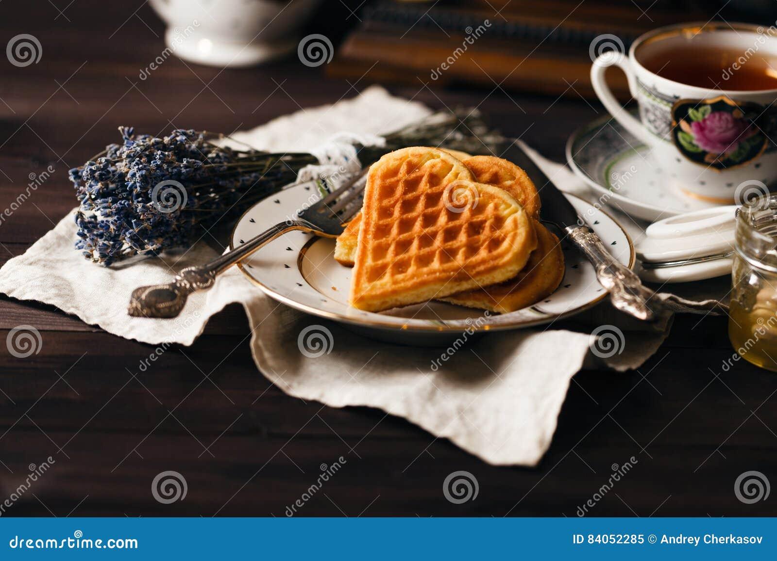 Wiedeńscy opłatki na zmroku stole z herbacianą filiżanką
