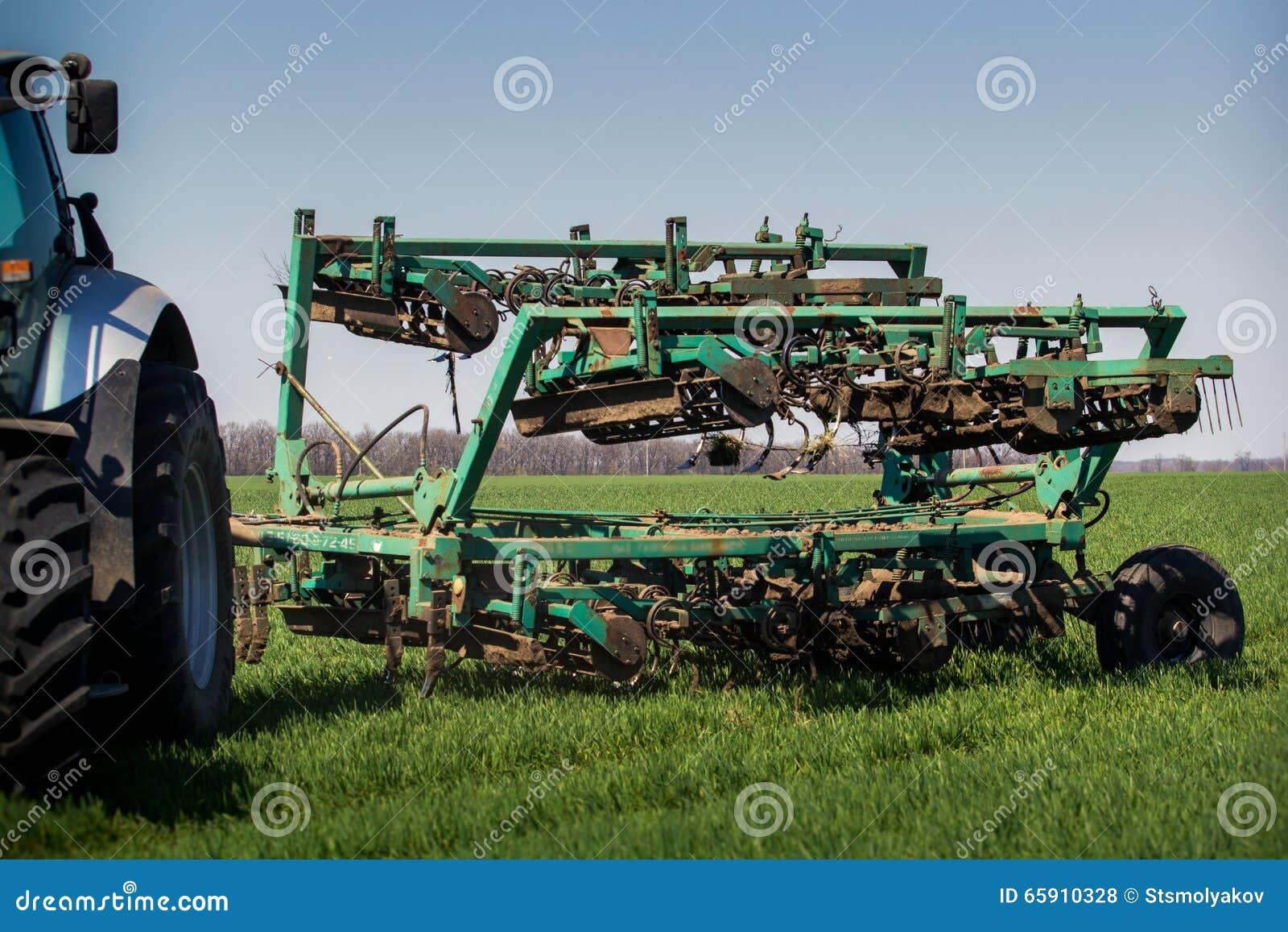 Wieden-machine achter tractor op groen tarwegebied