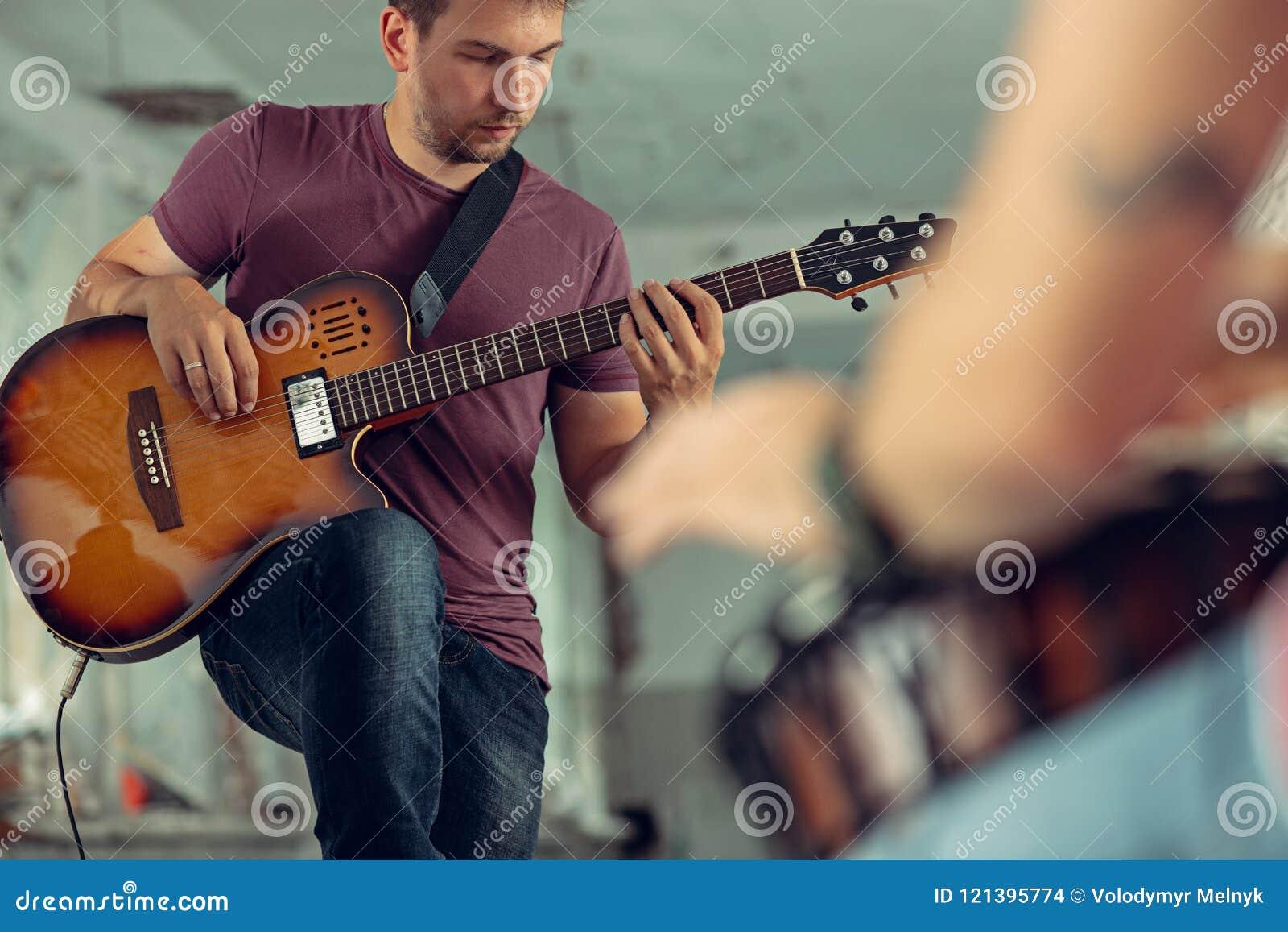 Wiederholung der Rockmusikband E-Gitarren-Spieler und Schlagzeuger hinter dem Trommelsatz