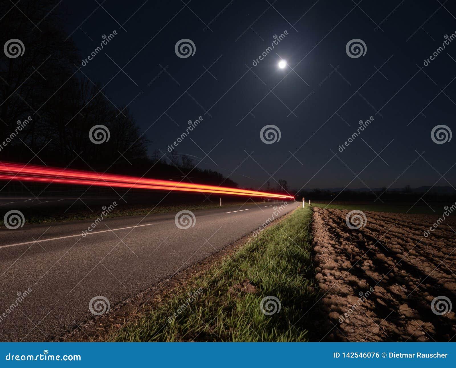Wiejska Droga przy nocą Iluminującą Przelotnym samochodem