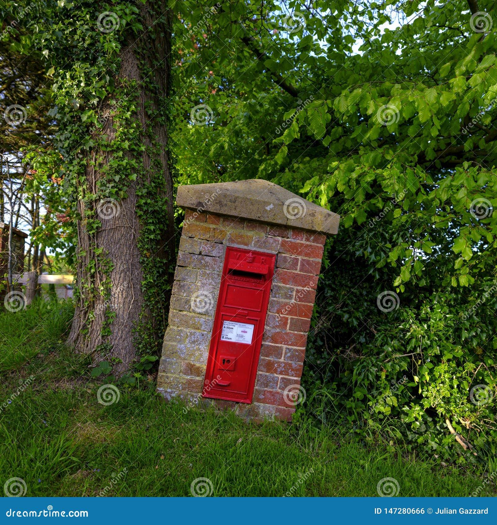 Wiejski postbox rusza się narastającym drzewem