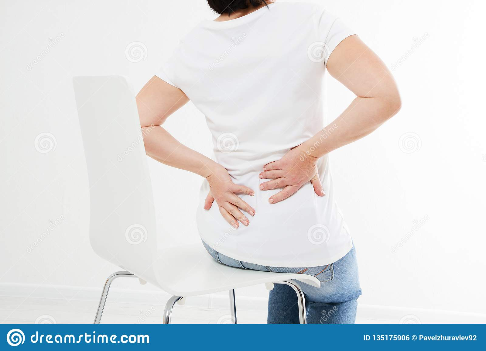 Wiek średni brunetki kobiety obsiadanie na krześle cierpi od tylnej obolałości, medycyna