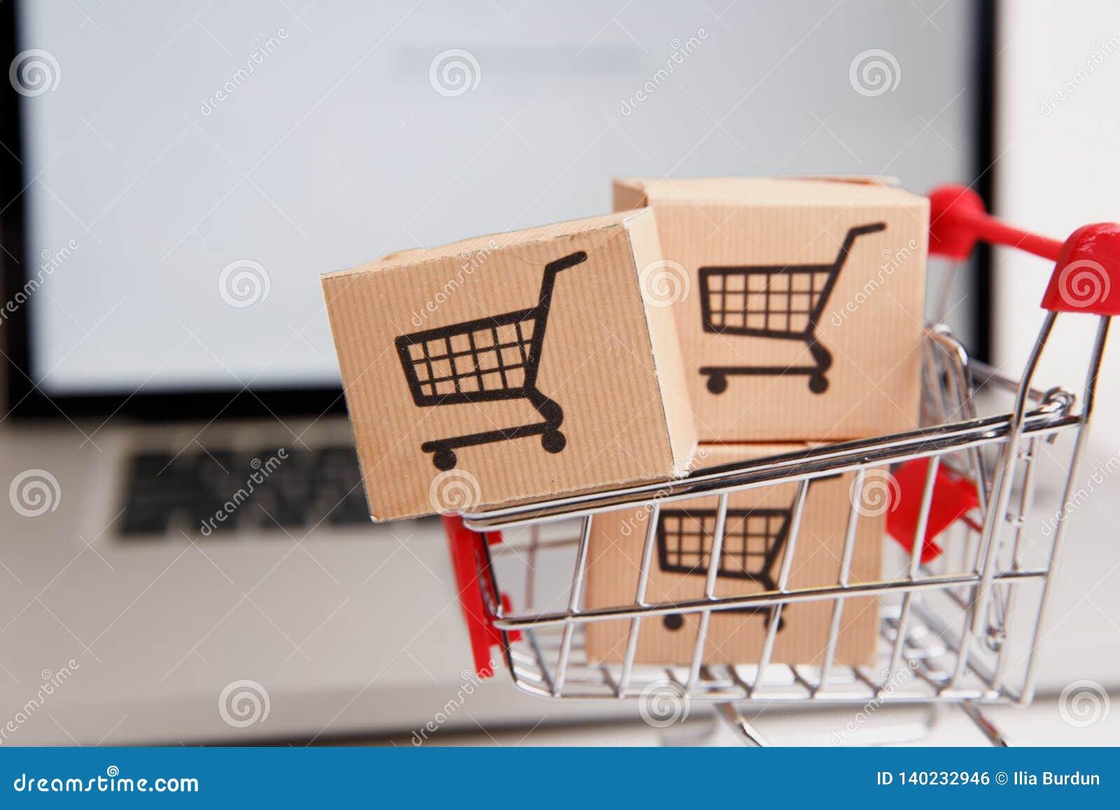 Wiele papierowi pudełka w małym wózku na zakupy na laptop klawiaturze Pojęcia o online zakupy który kupować mogą konsumenci