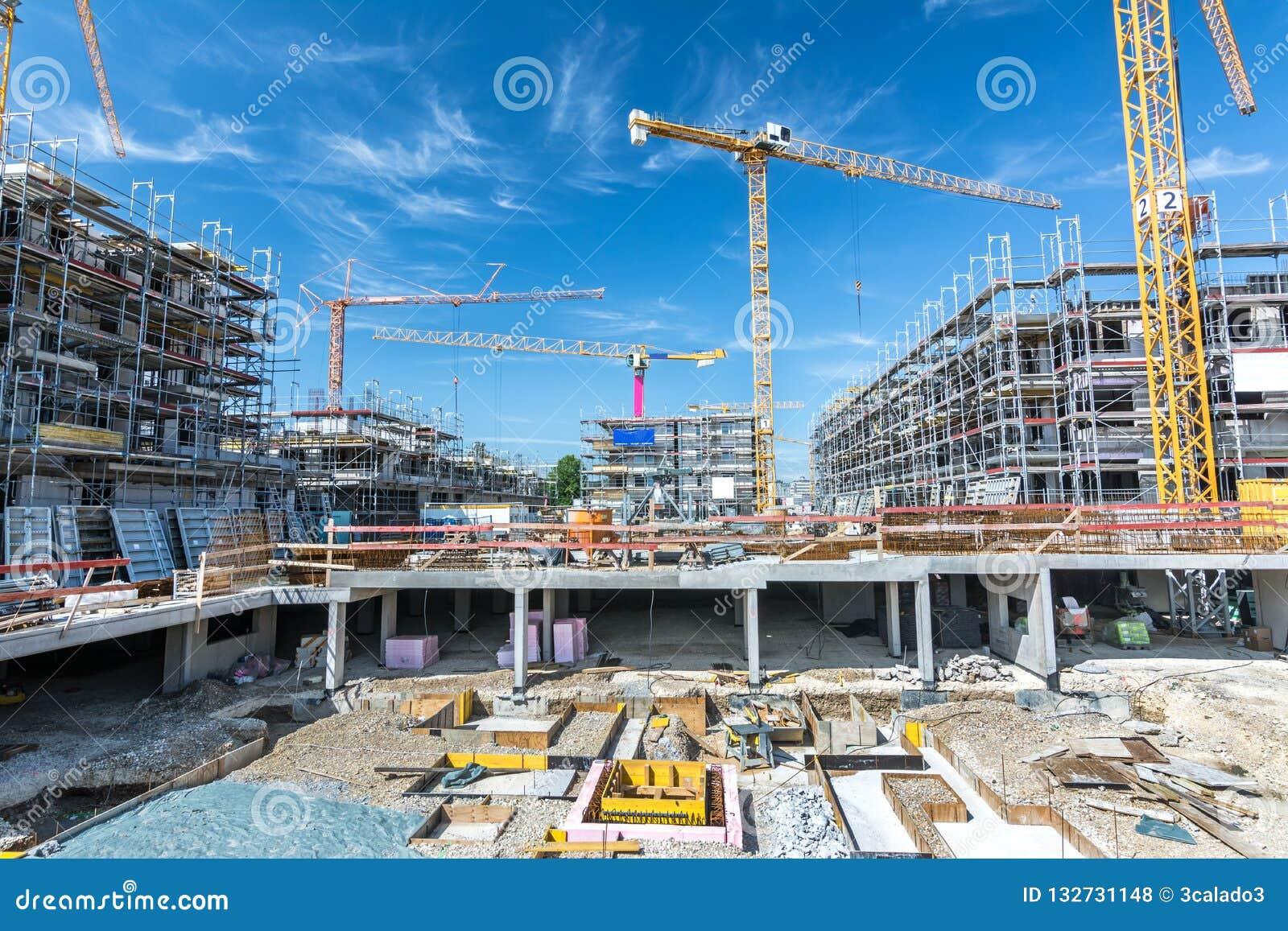 Wielka budowa z podstawami, rusztowaniem i żurawiami,