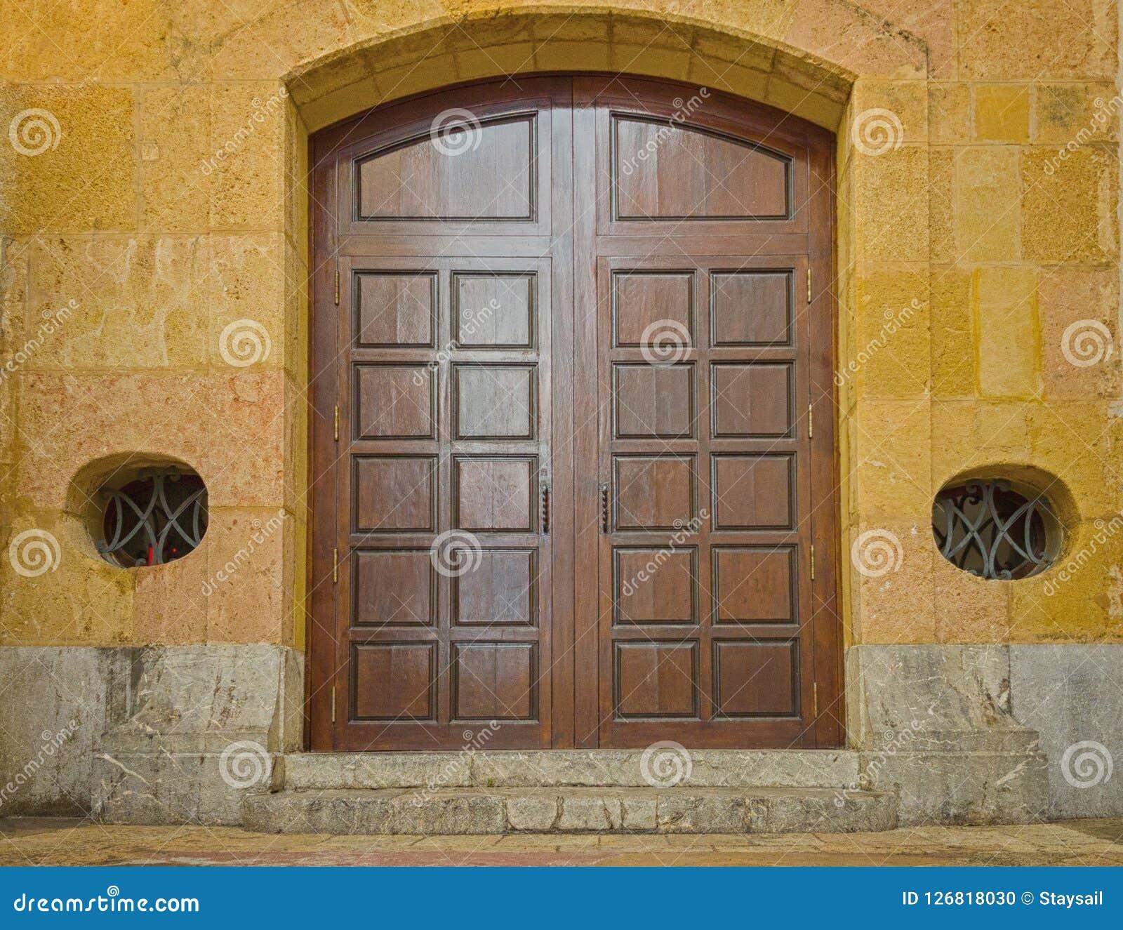 Wielka drewniana brama stary kamienny kościół