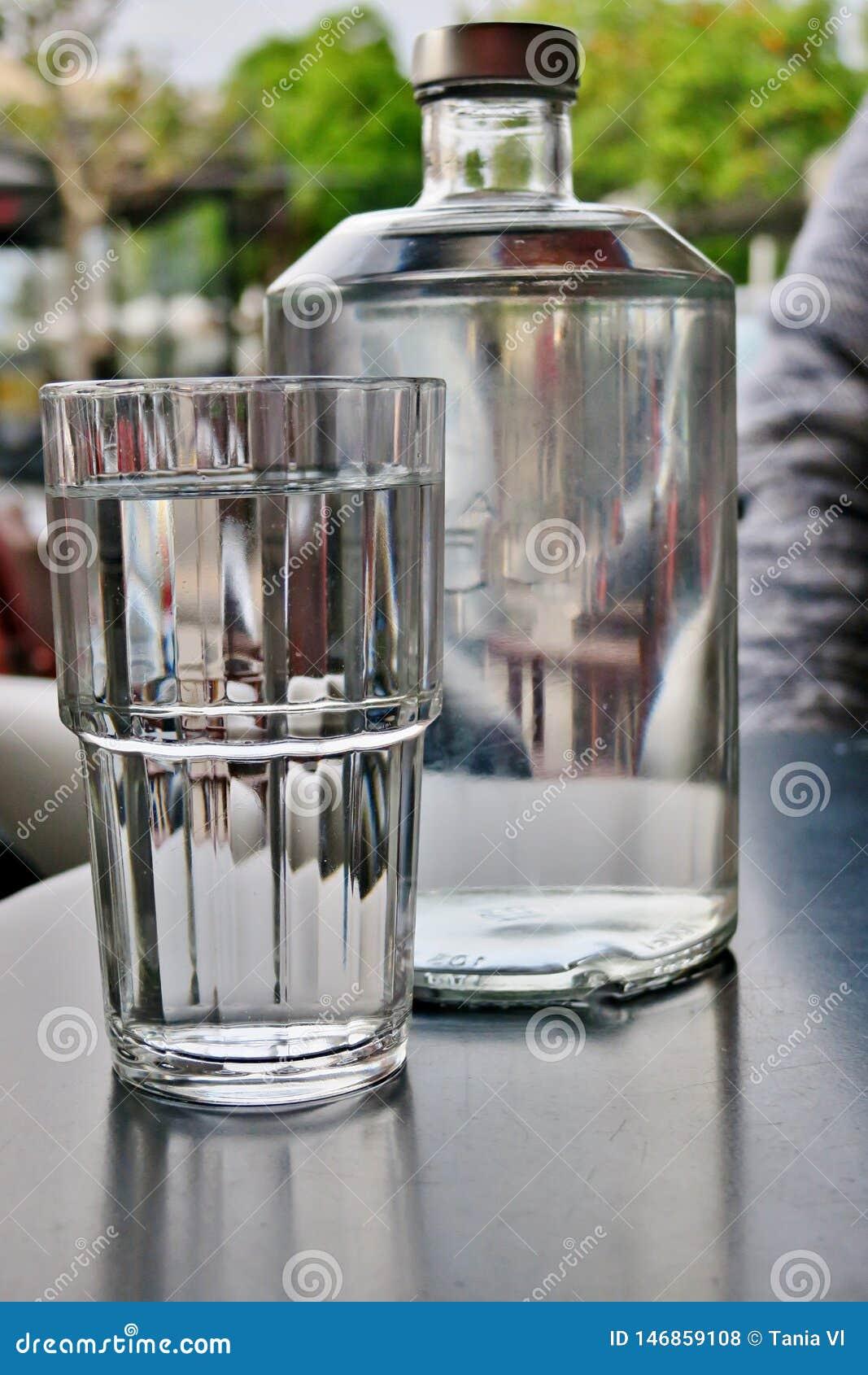 Wielka przejrzysta butelka woda z szklany nast?pnym, w g?r?