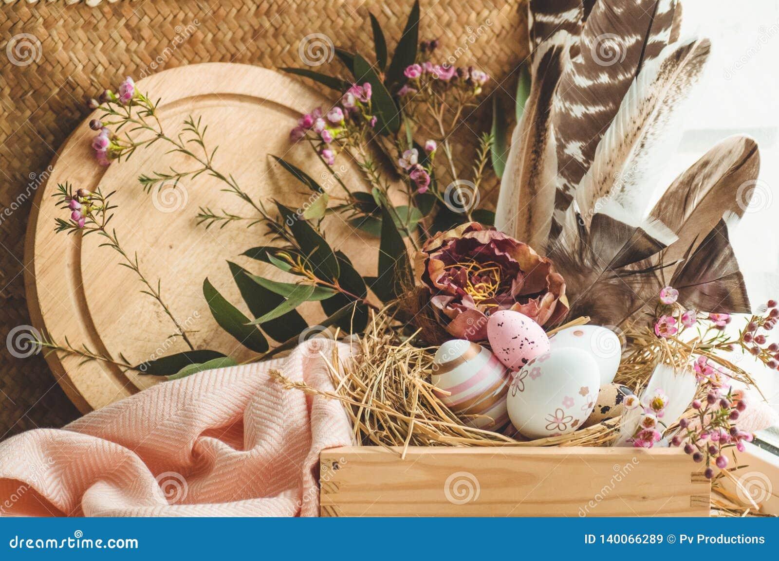 Wielkanoc tła szczęśliwy Różowi Wielkanocni jajka w gniazdeczku z kwiecistymi dekoracjami i piórkami blisko okno
